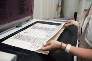 Screen printing a scarf with Maya Angelou's poem, Still I Rise.