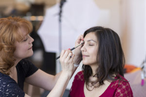 Creative professional tips - Makeup artist applying makeup to a woman's face